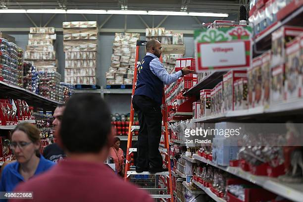 Jonathan Mary helps a customer at a Walmart store as they prepare for Black Friday shoppers on November 24 2015 in Miami Florida Black Friday which...