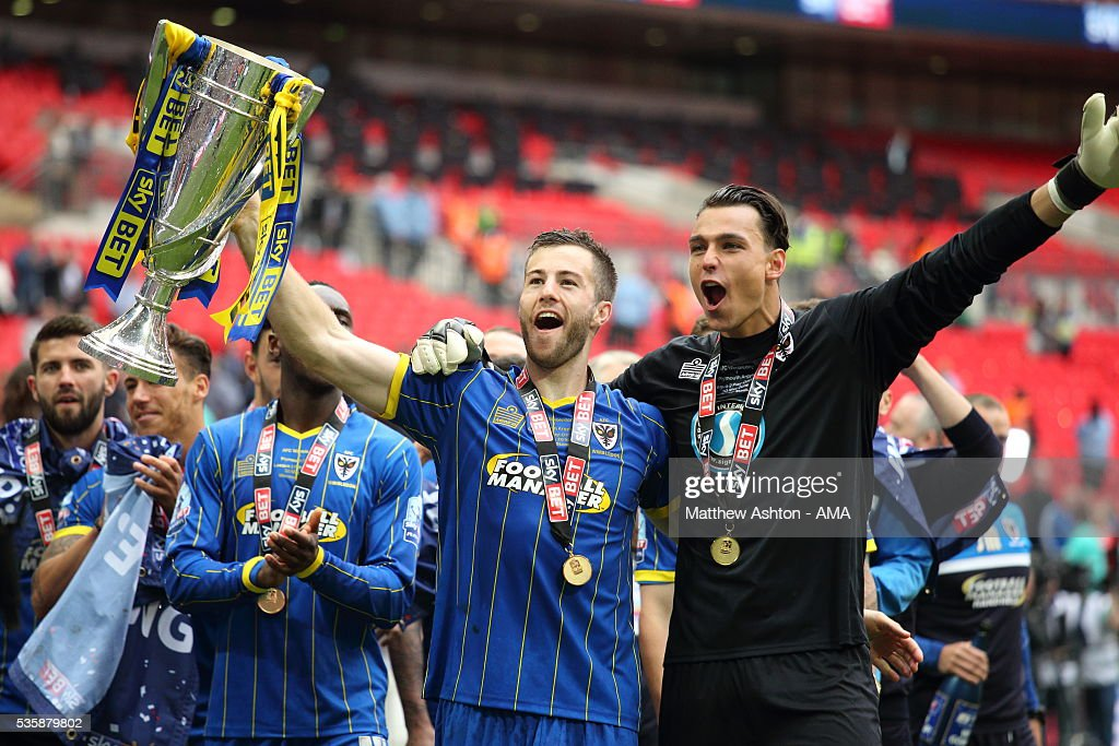 Jonathan Meades and Kelle Roos of AFC Wimbledon celebrate promotion with the trophy after victory in the Sky Bet League Two Play Off Final between Plymouth Argyle and AFC Wimbledon at Wembley Stadium on May 30, 2016 in London, England.