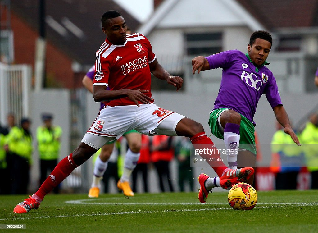 Jonathan Obika of Swindon Town and Korey Smith of Bristol City battle for the ball with during the Sky Bet League One match between Swindon Town and...