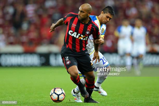 Jonathan of Brazil's Atletico Paranaense struggles for the ball with David Mendieta of Paraguay's Deportivo Capiata during their Libertadores Cup...