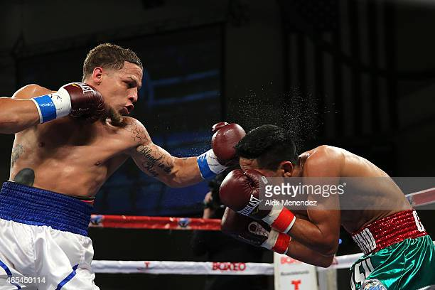 Jonathan Oquendo lands a left hook to the head of Gabino Cota as they fight for the WBO Latino Flyweight Title during the Telemundo Boxeo boxing...