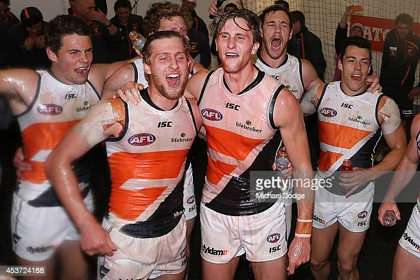 Jonathan O'Rourke of the Giants and James Stewart of the Giants celebrate their win during the round 21 AFL match between the Melbourne Demons and...