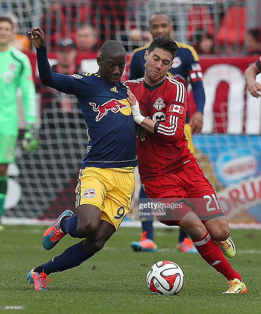 TORONTO, ON- MAY 17 - Jonathan Osorio and Bradley Wright-Phillips battle for the ball as Toronto FC beats the New York Red Bulls 2-0 at BMO Field in Toronto. May 17, 2014.