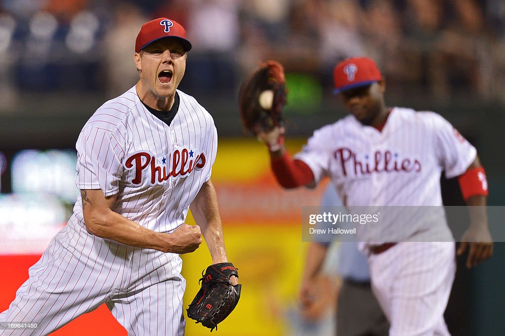 Jonathan Papelbon of the Philadelphia Phillies celebrates his 11th save of the season as Ryan Howard shows the ball after beating the Boston Red Sox...