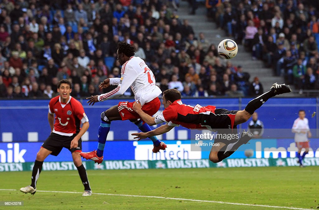 Jonathan Pitroipa of Hamburg and Steven Cherundolo of Hannover compete for the ball during the Bundesliga match between Hamburger SV and Hannover 96...
