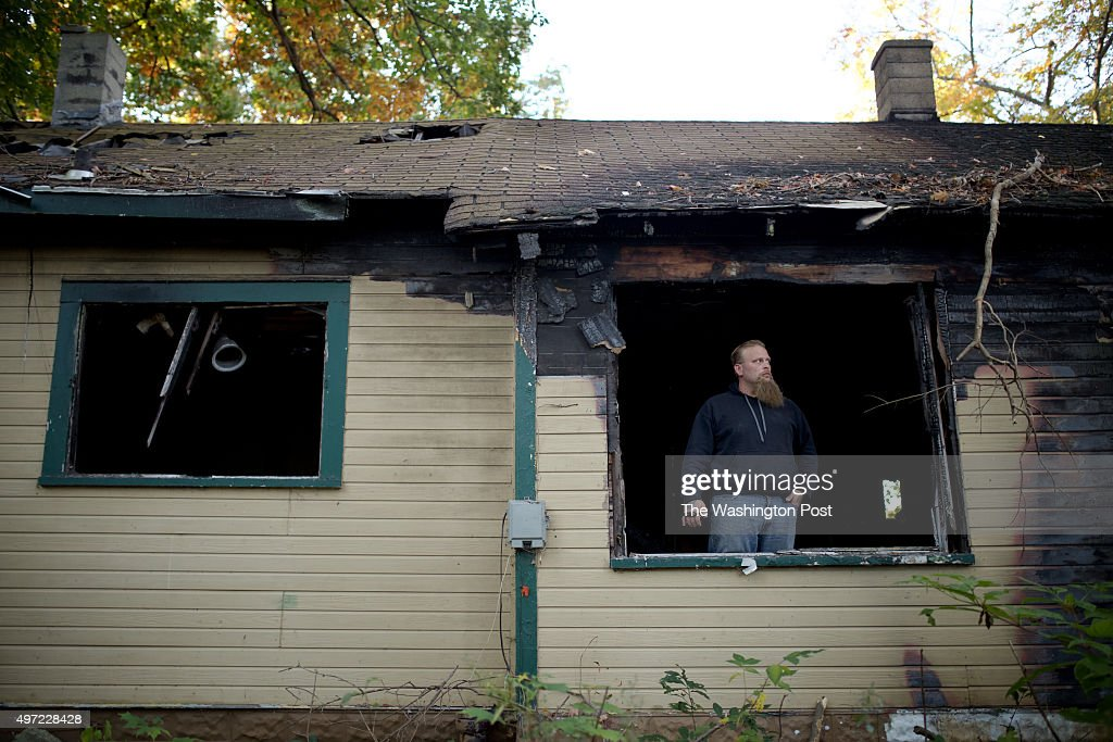 Jonathan Pommerville stands by a window of an abandoned house that was recently burned in his neighborhood of Brightmoor on October 15 2015 in...