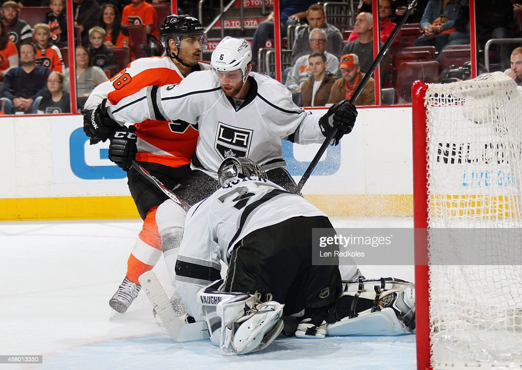 Jonathan Quick #32 of the Los Angeles Kings covers the puck as teammate Jake Muzzin #6 defends against Pierre-Edouard Bellemare #78 of the Philadelphia Flyers on October 28, 2014 at the Wells Fargo Center in Philadelphia, Pennsylvania. The Flyers defeated the Kings 3-2 in overtime.