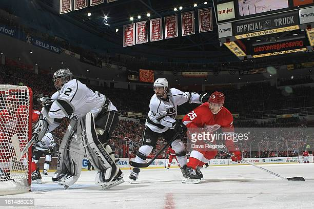 Jonathan Quick of the Los Angeles Kings follows the play while teammate Drew Doughty ties up Cory Emmerton of the Detroit Red Wings during a NHL game...
