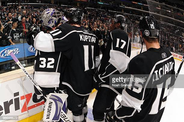 Jonathan Quick of the Los Angeles Kings is hugged by teammates Anze Kopitar Wayne Simmonds and Brad Richardson after being defeated by the Vancouver...