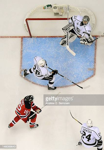 Jonathan Quick of the Los Angeles Kings makes a save in front of Slava Voynov Colin Fraser and Petr Sykora of the New Jersey Devils during the third...