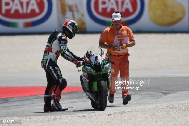 Jonathan Rea of Great Britain and KAWASAKI RACING TEAM check the condition of Chaz Davies of Great Britain and ARUBAIT RACINGDUCATI after crashed out...