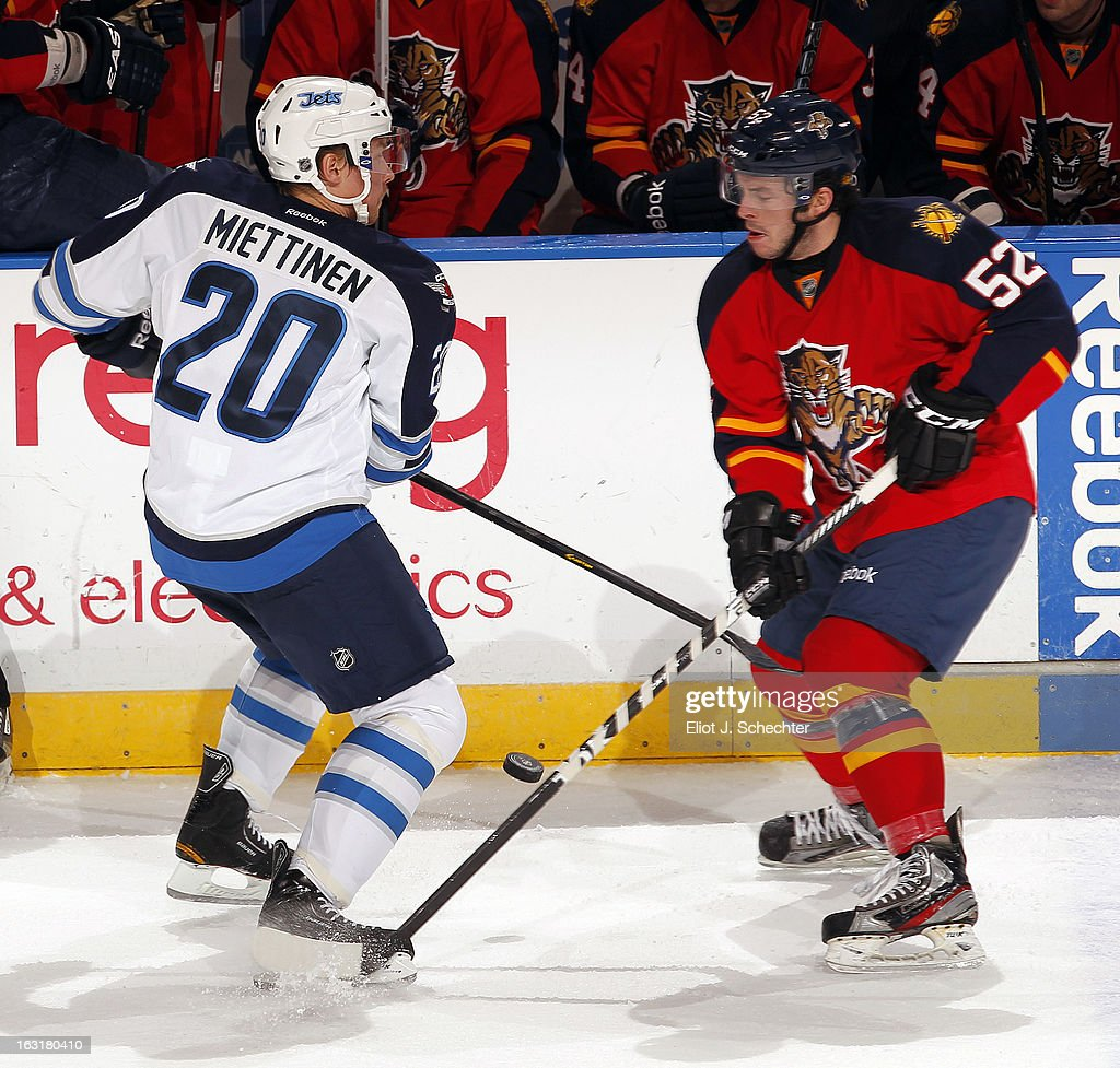 Jonathan Rheault #52 of the Florida Panthers, in his first NHL game, crosses sticks with <a gi-track='captionPersonalityLinkClicked' href=/galleries/search?phrase=Antti+Miettinen&family=editorial&specificpeople=576018 ng-click='$event.stopPropagation()'>Antti Miettinen</a> #20 of the Winnipeg Jets at the BB&T Center on March 5, 2013 in Sunrise, Florida.