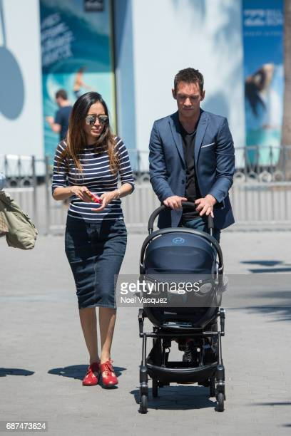 Jonathan Rhys Meyers and Mara Lane push a stroller carrying their son Wolf Rhys Meyers at 'Extra' at Universal Studios Hollywood on May 23 2017 in...