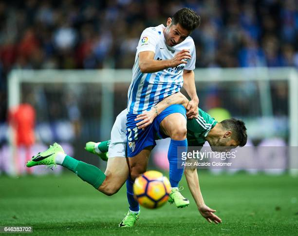 Jonathan Rodriguez of Malaga CF competes for the ball with Alvaro Cejudo of Real Betis Balompie during La Liga match between Malaga CF and Real Betis...