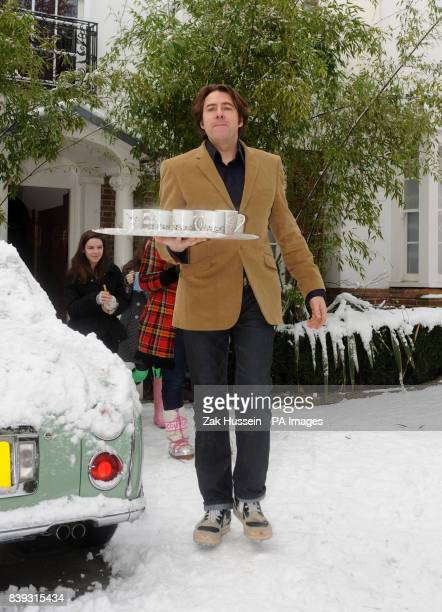 Jonathan Ross brings out cups of tea to the waiting media outside his home in north London after he announced that he is to quit the BBC