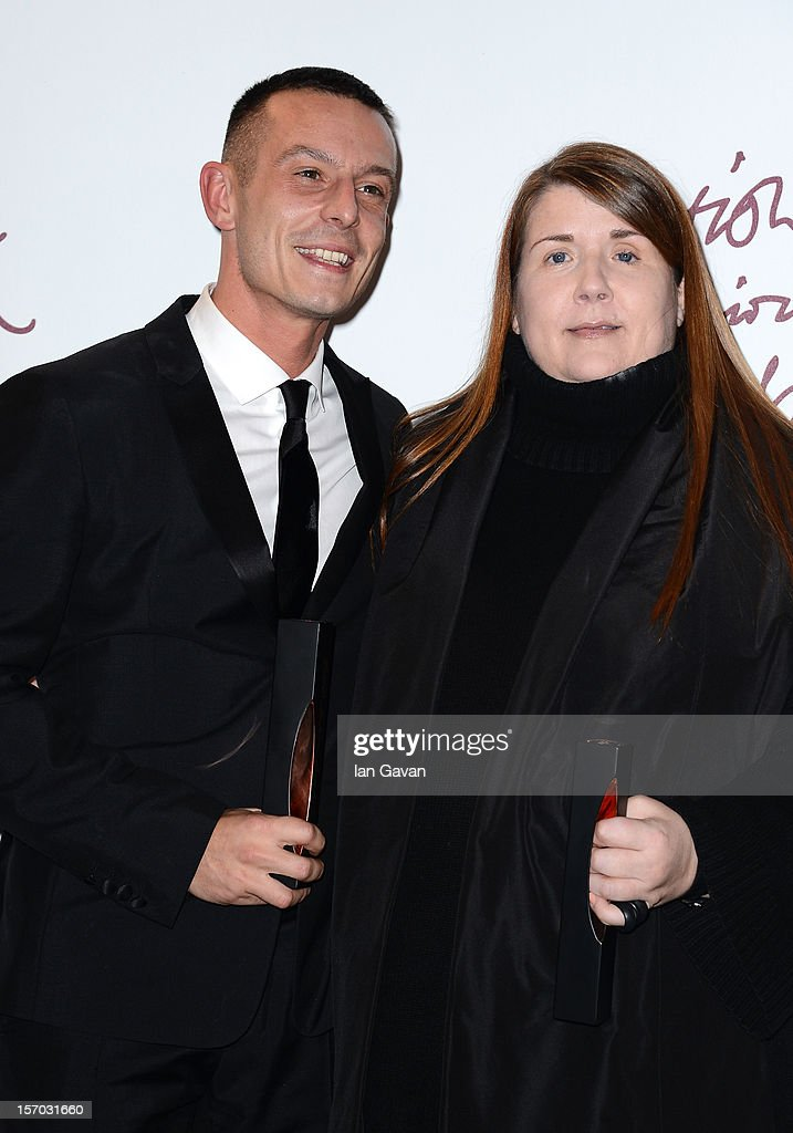 Jonathan Saunders (L), winner of the Emerging Talent - Menswear award, and <a gi-track='captionPersonalityLinkClicked' href=/galleries/search?phrase=Louise+Wilson+-+Fashion+Professor&family=editorial&specificpeople=12818171 ng-click='$event.stopPropagation()'>Louise Wilson</a>, winner of the Isabella Blow award for Fashion Creator pose in the awards room at the British Fashion Awards 2012 at The Savoy Hotel on November 27, 2012 in London, England.