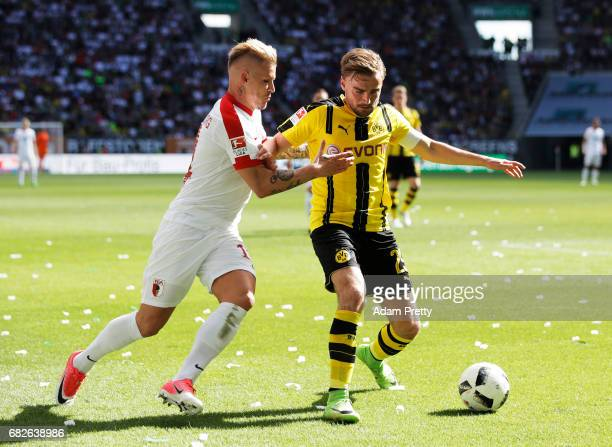 Jonathan Schmid of Augsburg challenges Marcel Schmelzer of Borussia Dortmund during the Bundesliga match between FC Augsburg and Borussia Dortmund at...