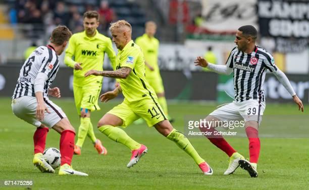 Jonathan Schmid of Augsburg in action against Omar Mascarell of Frankfurt and Bastian Oczipka of Frankfurt during the Bundesliga match between...