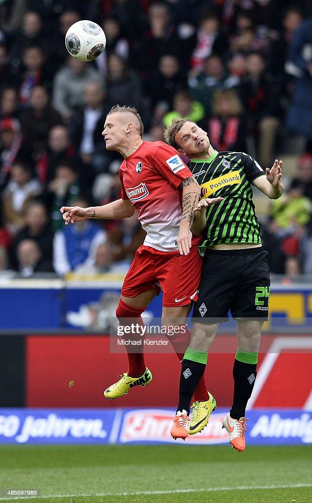Jonathan Schmid (L) of Freiburg challenges Tony Jantschke during the Bundesliga match between SC Freiburg and Borussia Moenchengladbach at Mage Solar Stadium on April 19, 2014 in Freiburg, Germany.