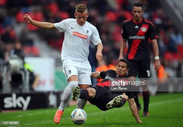 Jonathan Schmid of Freiburg is challenged by Michael Ortega of Leverkusen during the Bundesliga match between Bayer 04 Leverkusen and SC Freiburg at...