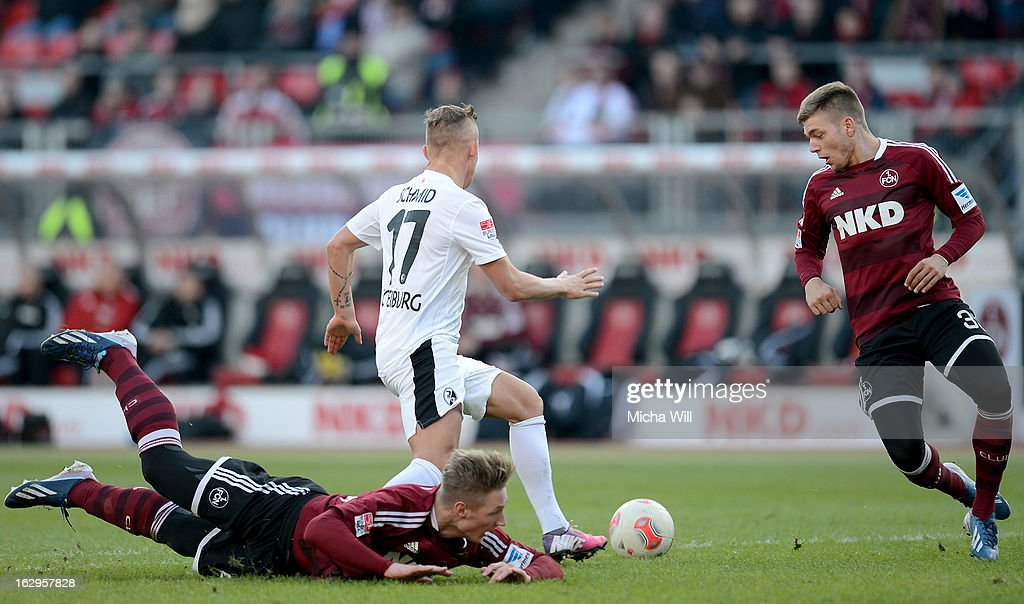 Jonathan Schmid (C) of Freiburg is challenged by Sebastian Polter (L) and Alexander Esswein of Nuernberg during the Bundesliga Match between 1. FC Nuernberg and SC Freibug at Grundig Stadion on March 2, 2013 in Nuremberg, Germany.