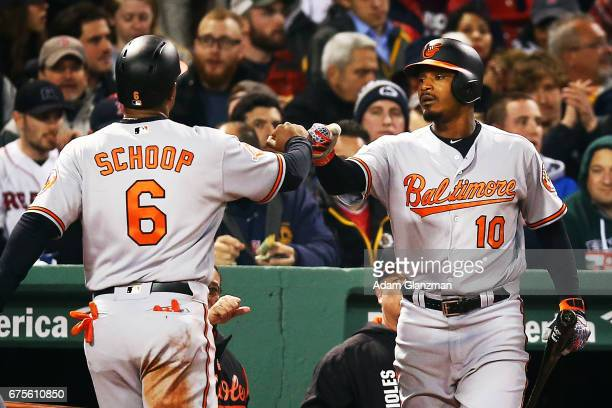 Jonathan Schoop high fives Adam Jones of the Baltmore Orioles after scoring in the fifth inning of a game against the Boston Red Sox at Fenway Park...