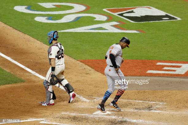 Jonathan Schoop of the Baltimore Orioles and the American League scores a run on an RBI single by Miguel Sano of the Minnesota Twins and the American...