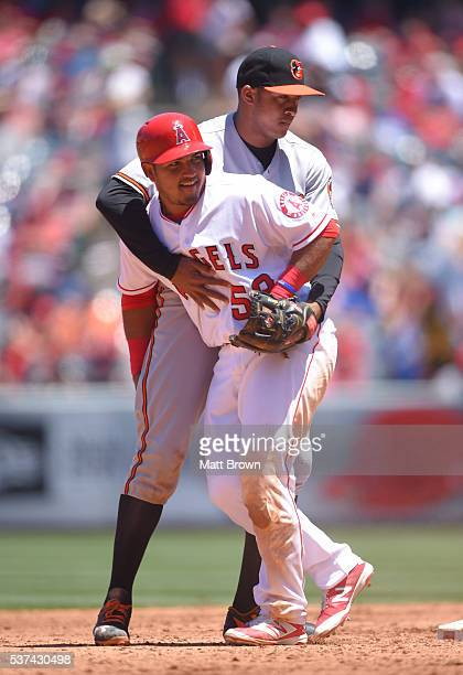 Jonathan Schoop of the Baltimore Orioles catches Carlos Perez of the Los Angeles Angels of Anaheim after he overslid second base during the third...