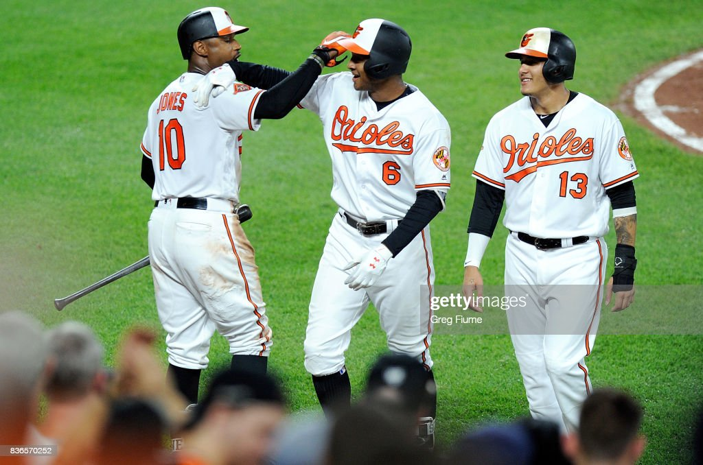 Jonathan Schoop #6 of the Baltimore Orioles celebrates with Adam Jones #10 and Manny Machado #13 after hitting a three-run home run in the fifth inning against the Oakland Athletics at Oriole Park at Camden Yards on August 21, 2017 in Baltimore, Maryland.
