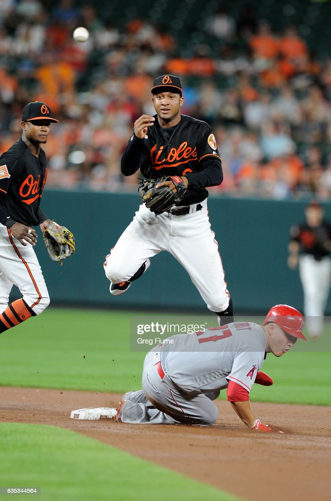Jonathan Schoop #6 of the Baltimore Orioles forces out Mike Trout #27 of the Los Angeles Angels to start a double play in the seventh inning at Oriole Park at Camden Yards on August 18, 2017 in Baltimore, Maryland.