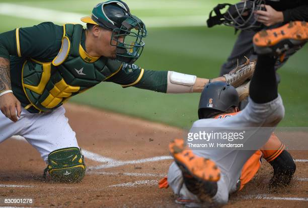 Jonathan Schoop of the Baltimore Orioles gets tagged out at home plate by Bruce Maxwell of the Oakland Athletics in the top of the first inning at...