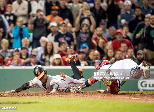 Jonathan Schoop of the Baltimore Orioles scores a run ahead of a tag by Sandy Leon of the Boston Red Sox in the fifth inning at Fenway Park on May 2...