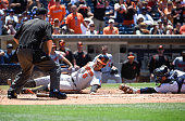 Jonathan Schoop of the Baltimore Orioles scores ahead of the tag of Derek Norris of the San Diego Padres during the fifth inning of a baseball game...