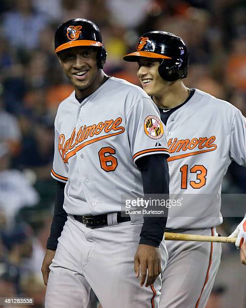 Jonathan Schoop of the Baltimore Orioles smiles with Manny Machado of the Baltimore Orioles after scoring against the Detroit Tigers on a single by...