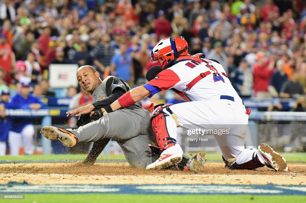 Jonathan Schoop #6 of the Netherlands slides into home as catcher Yadier Molina #4 of the Puerto Rico tags him out in the fifth inning during Game 1 of the Championship Round of the 2017 World Baseball Classic at Dodger Stadium on March 20, 2017 in Los Angeles, California.