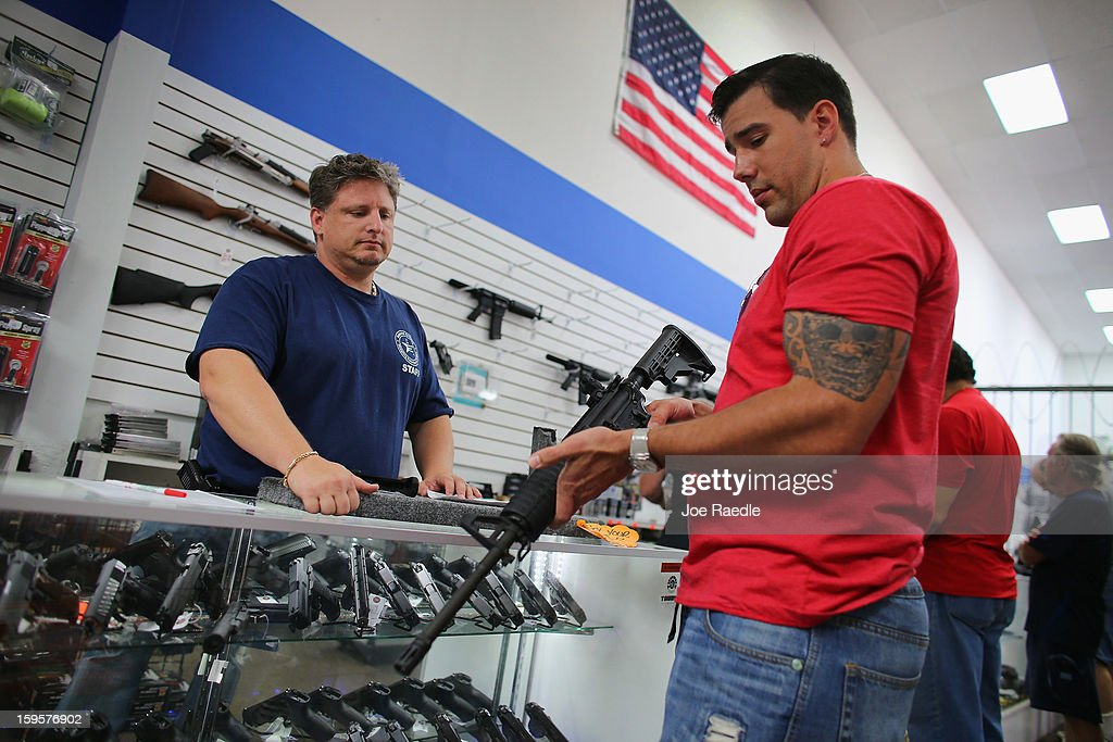 Jonathan Schwartz (L), a salesman at the National Armory gun store, helps Reese Magnant as he looks to buy a National Armory AR-15 Battle Entry Assault Rifle on January 16, 2013 in Pompano Beach, Florida. President Barack Obama today in Washington, DC announced a broad range of gun initiatives that his administration thinks will help curb gun violence.