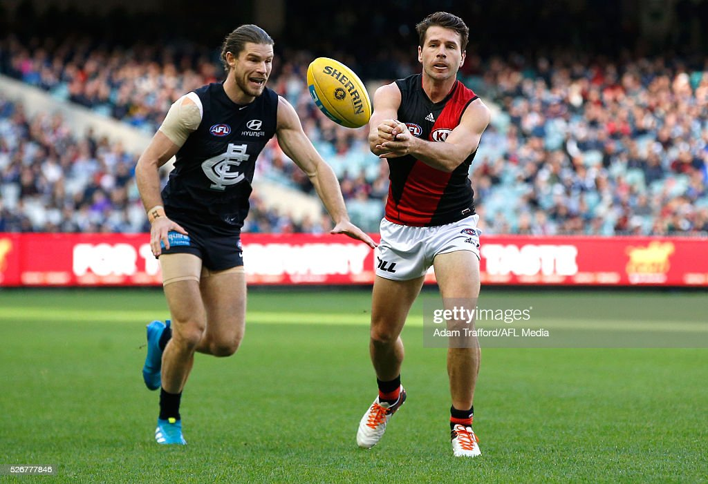 Jonathan Simpkin of the Bombers handpasses the ball ahead of Bryce Gibbs of the Blues during the 2016 AFL Round 06 match between the Carlton Blues and the Essendon Bombers at the Melbourne Cricket Ground, Melbourne on May 1, 2016.
