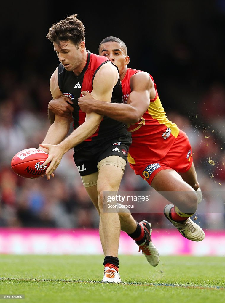 Jonathan Simpkin of the Bombers is tackled by Touk Miller of the Suns during the round 21 AFL match between the Essendon Bombers and the Gold Coast...
