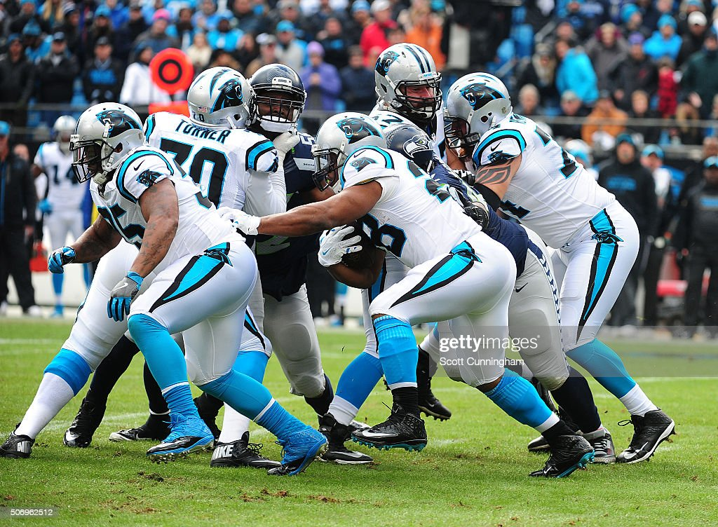 Jonathan Stewart of the Carolina Panthers carries the ball behind blocking by Mike Tolbert against the Seattle Seahawks during the NFC Divisional...
