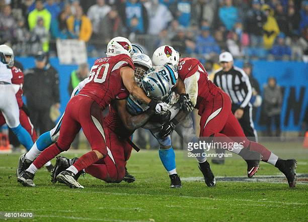 Jonathan Stewart of the Carolina Panthers is tackled by Calais Campbell Larry Foote and Marcus Benard of the Arizona Cardinals during the NFC Wild...