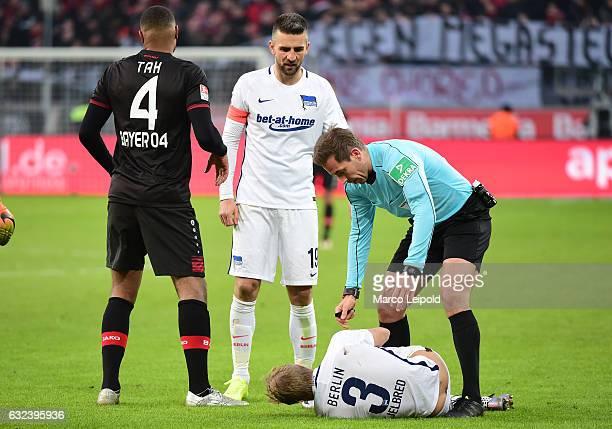 Jonathan Tah of Bayer 04 Leverkusen Vedad Ibisevic Per Skjelbred of Hertha BSC and referee Tobias Stieler during the game between Bayer 04 Leverkusen...