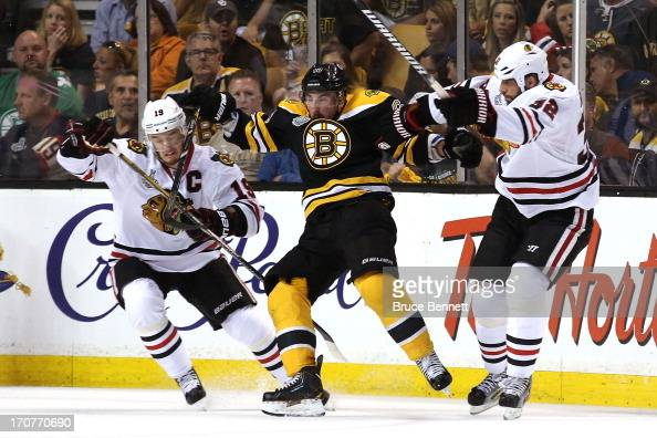 Jonathan Toews and Michal Rozsival of the Chicago Blackhawks collide with Brad Marchand of the Boston Bruins during the first period in Game Three of...