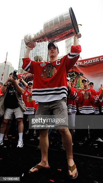 Jonathan Toews holds up the Stanley Cup trophy during the Chicago Blackhawks Stanley Cup victory parade and rally on June 11 2010 in Chicago Illinois