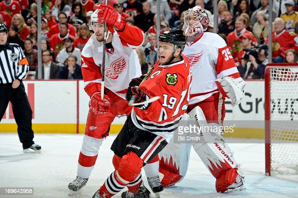 Jonathan Toews of the Chicago Blackhawks and Brendan Smith of the Detroit Red Wings watch for the puck in front of goalie Jimmy Howard of the Red...