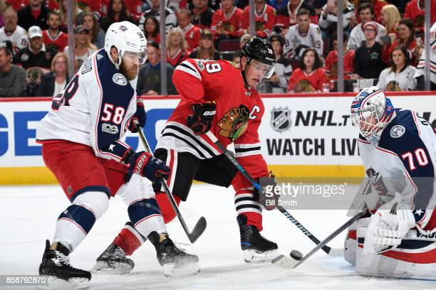 Jonathan Toews of the Chicago Blackhawks and David Savard of the Columbus Blue Jackets chase the puck toward goalie Joonas Korpisalo in the first...