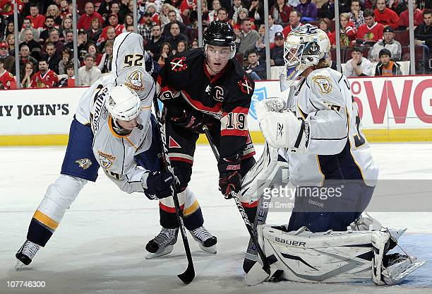 Jonathan Toews of the Chicago Blackhawks and Jerred Smithson of the Nashville Predators look for the puck in front of Nashville goalie Anders...