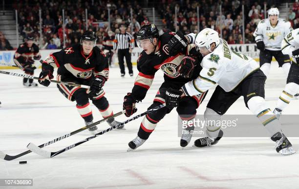 Jonathan Toews of the Chicago Blackhawks and Matt Niskanen of the Dallas Stars reach for the puck as Jeremy Morin of the Blackhawks skates up the ice...