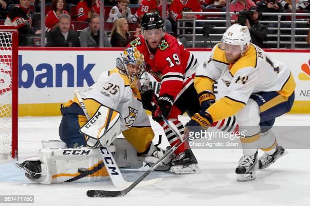 Jonathan Toews of the Chicago Blackhawks and Mattias Ekholm of the Nashville Predators battle for the puck next to goalie Pekka Rinne in the second...