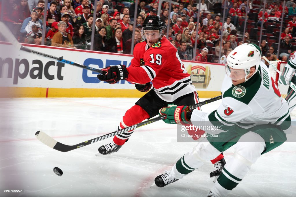 Jonathan Toews #19 of the Chicago Blackhawks and Mikko Koivu #9 of the Minnesota Wild chase the puck in the second period at the United Center on October 12, 2017 in Chicago, Illinois.