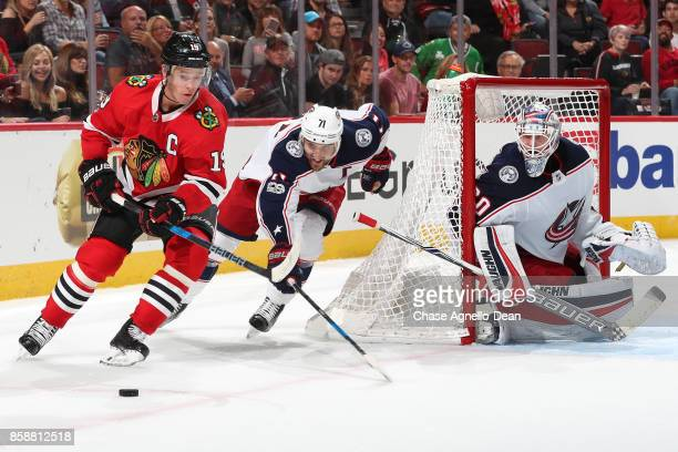 Jonathan Toews of the Chicago Blackhawks and Nick Foligno of the Columbus Blue Jackets chase the puck around the net guarded by goalie Joonas...